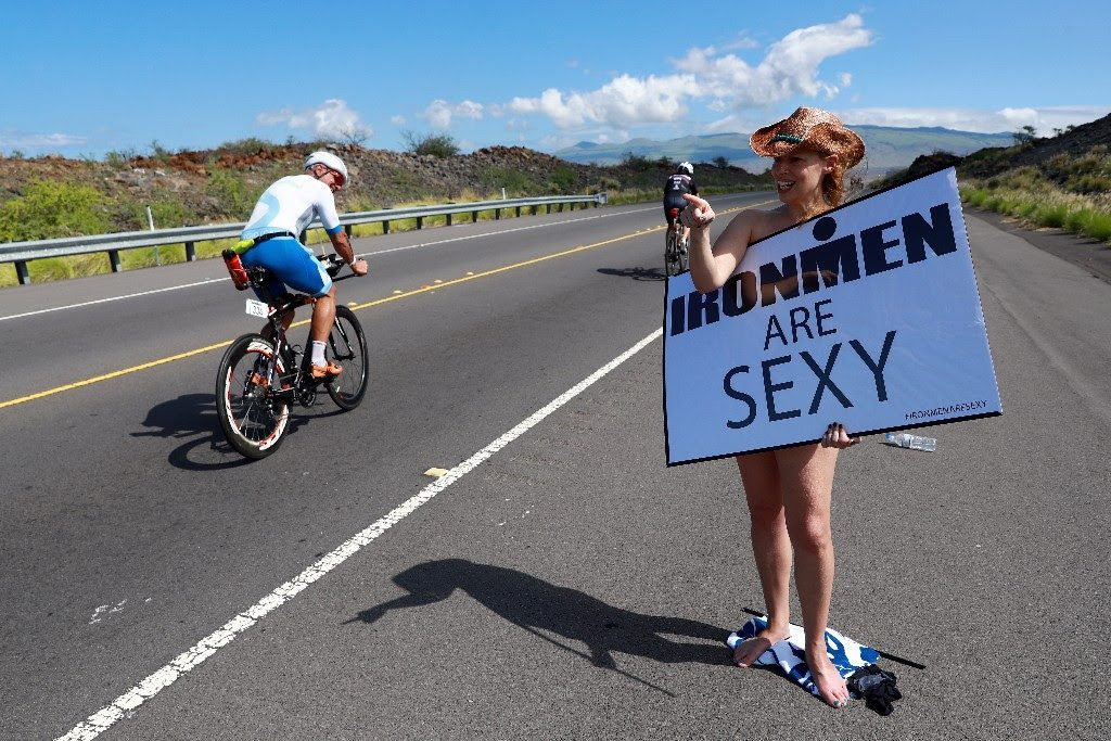 HONEST SUPPORT: Michelle Alexander from Denver holds up an 'IRONMEN ARE SEXY' sign as athletes cycle by at the IRONMAN World Championship on October 14, 2017. (Photo by Tom Pennington/Getty Images for IRONMAN)