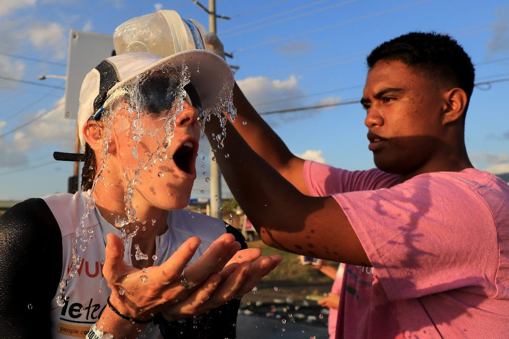 LOOKING COOL: An athlete at the IRONMAN World Championship has water poured on her head by one of the 5,000 volunteers to help combat the 87F/31C heat experienced on the 26.2 mile run course in Kailua-Kona, Hawai`i. (Photo by Sean M. Haffey/Getty Images for IRONMAN)